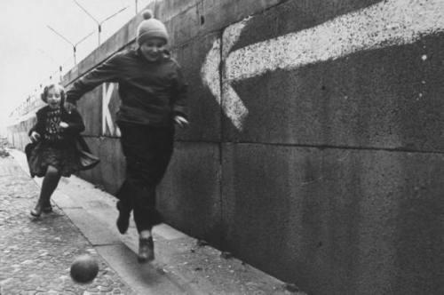 bestoflife:  Berlin Wall. Young boy & girl playing soccer next to the Berlin wall. December 1962, Paul Schutzer
