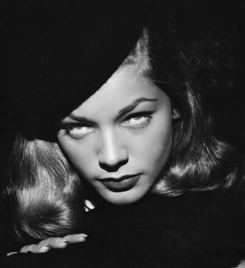 Lauren Bacall in publicity still for The Big Sleep (1946, dir. Howard Hawks) She was worth a stare. She was trouble.  She was tall and rangy and strong-looking. She had a good mouth and a good chin. There was a sulky droop to her lips and the lower lip was full. She had a drink. She took a swallow from it and gave me a cool level stare over the rim of the glass.  -Raymond Chandler, The Big Sleep (1939)