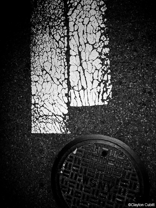 claytoncubitt:  Cracked crosswalk guides and manhole cover, Brooklyn See also: Tire treads in fresh snow, Brooklyn