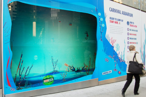 BizBash | Carnival Cruise Lines Woos Travelers With Virtual Aquariums in Six Cities These are computer-animated fish tanks in vacant storefronts along sidewalks in big US cities to advertise Carnival cruises. Passerby can text the number on the screen and then control the swimming patterns of the fish inside the aquarium by texting in commands. Elements inside the aquarium are also set off by motion detectors, so for example seaweed waves when somebody walks by. Again, increasing interactivity within advertising methods. - cthrin