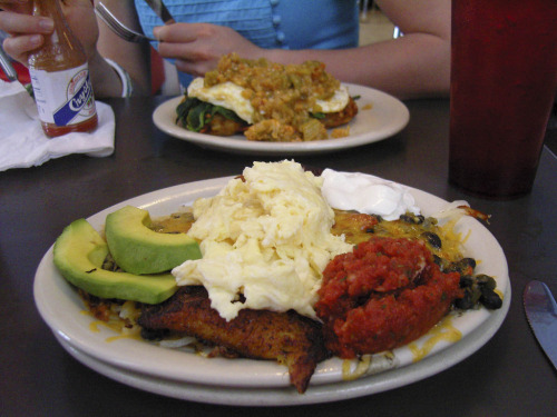 Slim Goodies in Nola In the foreground: black beans, mashed potatoes, latkes, and avocado with melted cheese, sour cream, and salsa. In the background: two fried eggs with spinach on latkes served with crawfish étouffée.