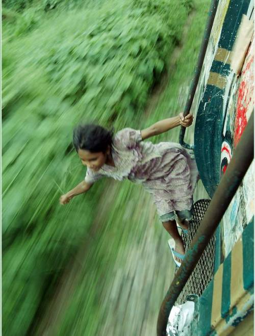 reginasworld:  A girl playfully hangs from the door handle of a train, in Chittagong, Bangladesh. Aftab Tuhin, photographer  (via findout)