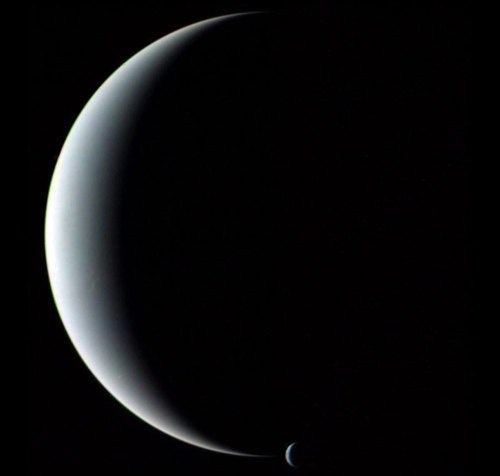 Neptune and Triton Gliding silently through the outer Solar System, the Voyager 2 spacecraft camera captured Neptune and Triton together in crescent phase in 1989.  via spacefellowship.com