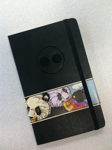 These are the custom Moleskines I designed for Flickr. It was a bit tricky finding a debosser in the area (we didn't), so if you're interested in getting a custom Moleskine for your company, read on.  We bought the Moleskines on Amazon and shipped them directly to the debossers, C&S Printers in New Jersey. (They also debossed the Wordpress Moleskines).  A local company, Spotlight Design & Print, printed the wraps and shipped them to C&S for finishing.  Edit: The artwork for the wrap comes from the Searcher's amazing  Rainbow Vomiting Pandas Of Interestingness, which he kindly agreed to let us use.  The whole process took about three weeks. The vendors were responsive, reasonably priced* and met their deadlines.  *They were reasonably priced for what we got, I mean. Neither Moleskines nor debossing is cheap.