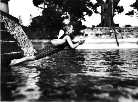 "Dé        Dé / France 1911 by Jacques HENRI LARTIGUE DADDY SMOKED MARLBOROS. Daddy whisked the boy away to Cavalaire for the summer.  Unlike every other child in the family, the young boy was separated from his father by not only the Atlantic ocean; but, hundreds of thousands of life shaping moments for which father would never be present.  It was imperative that the child witness and appreciate what it is to be a loved by his father.  These few precious moments they spent together had to count for all the times he was not in attendance.  Papa insisted on it.  The absolute best of everything would be paramount on this trip: large home near the beach, boat rental to discover nooks and crannies around the picturesque coastline, incredible French traditional foods (not that processed crap his mother fed him in America).  Most of the French family the boy loved so dearly managed to be in attendance.  They set off on the nine hundred Kilometer trip from Paris on a Friday.  Father, son, and beloved cousin, Margot, in the back seat.  The boy was ecstatic.  He had escaped the clutches of his mentally unstable mother in America; as well as, the abuse he sustained from his tormentors in school (if only for the summer).  When his daddy was present, the boy felt loved.  Truly loved.  Months later the boy would cry himself to sleep thinking of the drive for weeks on end; making sure to bury his face in his wet pillow least he be heard by his mother.  He would recall the stubble on Papa's face in contrast to the half opened car window.  He would remember the endearing smile father would bless upon the boy, all while puffing away on a Marlboro light.  When he thought of that half cocked smile, Marlboro balanced seamlessly on his lips, the boy would receive a jolt of grief and cry out for his daddy without making a sound.  Just the hush emanating from his lips, ""papa,"" as the tears poured and his body quaked with grief.  The reality of a father's cowardice and his inability as a provider is never contemplated by a child who sees him but for fraction of the year.  All is a wonderful fairy tale when the rigors of a normal life are replaced by boats and sandy beaches.  The boy built the mythology unknowingly.  Father let him. Weeks later the family had settled into their large home by the beach.  They had explored nearly every alcove and island in the region.  The boy blushed and marveled at the beautiful half naked women strutting about.  Such ""things"" would never be exposed in Texas.  Most of all the boy was mesmerized by the ocean water.  Its clarity was as foreign to him as unconditional love he was experiencing from his French progenitors.  Mother had dutifully taken him to the local coastal cesspool by the port.  He remembered forming sand castles from the polluted mud and standing in six inches of water, unable to see his feet.  By comparison, In this paradise, he swam in the thick patches of seaweed, plucking starfish off the ocean floor.  He danced on the deck of the boat with his cousins screaming at the top of his lungs: ""She loves you, yeah, yeah, yeah!""  The thick French accent emanating from the others was amusing to him.  How he loved them he thought to himself.  He never wanted the summer to end.  The family gathered around the table on the patio for every delicious meal they savored whilst in the home.  Fresh tomatoes sprinkled with olive oil and topped with fresh mozzarella, whole farm raised chickens cooked to absolute perfection.  Their skin covered with assorted herbs and seasoning that the boy considered exotic.  At least four bottles of wine were consumed amongst the patriarchs every evening.  Father made sure to pour his loving son a small glass every night in hopes the elixir would coax whatever trace of his European genes lay dormant in the boy's psyche.  Often, he would have conversations with his sister about the boy when he assumed the child was out of earshot.  The little man listened in one evening as his hero voiced concerns about his uncultured and Americanized spawn.  Concepts which flew over the child's comprehension level; but, he felt the anxiety in his father's voice non the less.  Fear penetrated the boy's heart.  He attempted, to the best of his ability, to suppress the emotional duress.  He was seized by his mother.  Five thousand miles away, and he was already home from the summer holiday."