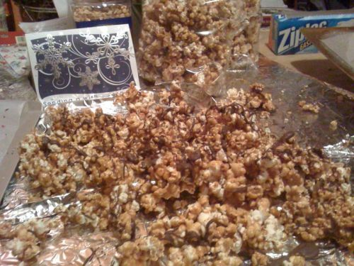 "Joyce's Caramel Corn Recipe Looking to make some last minute Christmas gifts for family and friends? This recipe from my mother-in-law has become a go to for us (Liz made seven batches on Tuesday night when we set up ""Santa's Kitchen Workshop""). This also works for an easy—yet impressive everyday treat. Bring it to parties and it's an instant hit! Recipe 5 c popped popcorn 1 stick unsalted butter 1 cup peanuts (optional) 1 c brown sugar 1/3 c light corn syrup Pinch of salt 1 scant tsp baking soda  Pop popcorn and spread with peanuts on a rimmed baking sheet.   Combine butter, corn syrup, and salt in saucepan. Stir over medium heat, then bring to a boil. When mixture reaches a boil, let it boil for 5 minutes WITHOUT STIRRING.   Remove from heat an stir in a scant teaspoon of baking soda. Stir/whisk until foaming.   Pour caramel mixture over popcorn and peanuts, and mix with a spoon. Bake at 275 for 30 minutes, stirring every 10 minutes.   Place on wax paper to cool. (Optional, drizzle with melted chocolate, we use milk chocolate ""bark,"" because it cools and hardens quickly)."