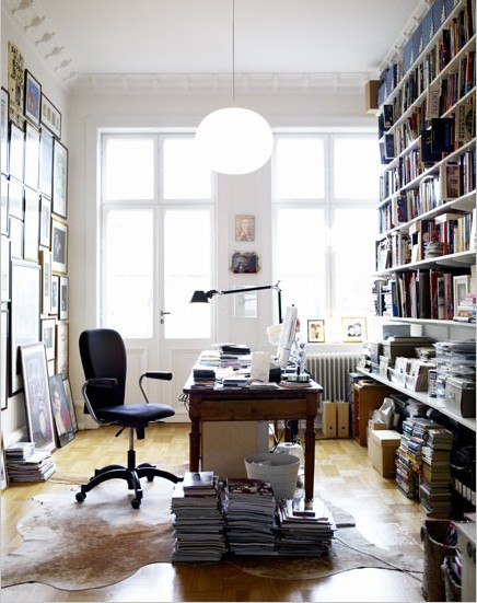 Something very appealing about the desk in the middle with a wall of books and another wall of pictures. And those windows with that beautiful light.