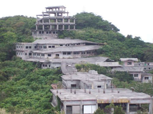 Ruins of Kogen Hotel (Takahara Hotel), near Nakagusuku Castle ruins, Okinawa, Japan, January 2010 Okinawa is home to dozens of ruined vegetation covered castles, and now that the weather is no longer brutally hot, its interesting to explore them.  Most of them arent very exciting, just sections of walls built back up and empty enclosed courtyards, but the one in Nakagusuku, which I hadnt visited before, is my new favorite.  It was built in the 15th century, and is on a very high point on Okinawa where you can see both the Pacific Ocean and the East China Sea, depending on which direction you are looking.  Macbeth would have said it hath a pleasant seat. In addition to sweeping panoramic views, it had a number of nooks and crannies and shrines and caves, including a steep, stone staircase that led down to a well, which was still full of clear water.  The well itself was kind of creepy&the air around it was really really cold.  There was a noticeable temperature difference between the top and the bottom of the stairs, even though it was all outdoors. At this point the castle site was almost about to close for the day, but towards the very back of the ruins, one could see the reputedly haunted remains of the Royal Hotel, about 50 yards away.  I tried to get as close as I could for the photo, and might have crawled onto the top of a wall behind a primitive safety barrier *whistles*, but it was just too interesting to pass up.  I sat there in the bleak afternoon&and I tried to see how one could approach the hotel itself, on a future trip.  The ruins themselves are really creepy looking&and as I sat there, I heard a mysterious howling moaning sound coming from inside them.  I would like to say that it was probably a dog&but what if it wasnt? The back story that I could glean says the hotel was built in the 1970s by a businessman from Naha, Okinawas capital, who wanted to capitalize on the sites location next to the castle ruins.  Villagers told him that the area was sacred (there are many many old and forgotten tombs there in the jungle), but he spent millions on his hotel, which had sort of a haphazard layout, reputedly without any sort of blueprints.  Stairs led to nowhere in a maze of hallways. Some Buddhist monks from a nearby temple came and told him that he was building too close to a sacred cave with restless spirits in it, but he refused to stop.  Some workers left after they heard the warnings, and still more left after their fellow workmen were killed in a series of mysterious accidents.  Finally, the businessman decided to prove his hotel was not haunted by spending every night there until construction was finished.  He lasted three nights, went insane, became bankrupt and was committed at an institution on the island or, some stories say, he killed himself two weeks later. Another rumor says a monk took up residence in the hotel ruins and built an altar, in order to appease the restless spirits.  Another section of the hotel was thought to have been used as a brothel, and bears the marks of a mysterious fierce fire.  Apparently, there are still rooms full of abandoned furniture and ragged curtains and tatami mats and all kinds of creepiness&and of course, I sort of have a itching to go see it myself, although its probably a foolish idea.  We shall see. (Finally visited here.)