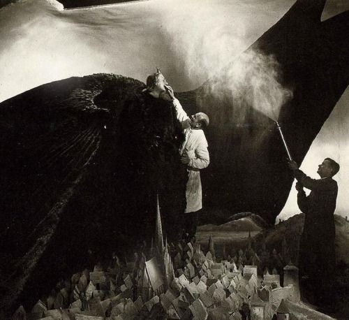 Crew members prepare Emil Jannings for the scene in Faust (1926, dir. F.W. Murnau) in which Mephisto's wings obscure the sky as he hovers above a city. (via)