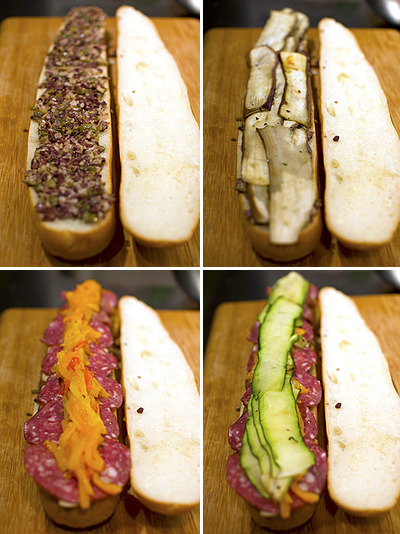 Tapenade salami sandwichSandwich 1 Asian Eggplant 1 Zucchini 2 large (or 4 small) Sweet Bell Peppers 1 cup Manchego Cheese, grated Salami (optional) 1 Baguette  Tapenade 1/2 cup olives, pitted 2 cloves of garlic 3 tbs capers 1/4 cup extra virgin olive oil 1 squeeze of lemon juice  Quick TapenadeChop and combine.SandwichPreheat oven to 450°F.Roast the bell peppers and slice into strips.Slice the zuchinni and eggplant thinly using a vegetable peeler or a sharp knife. Toss in olive oil, salt, and pepper. Spread them out on a foil-lined baking pan and roast in the oven for 10 minutes. Flip them half way.Slice the baguette in half lengthwise. Brush with olive oil and toast briefly for 1 minute.Spread the tapenade on the bottom baguette slice. Top with eggplant, salami, bell peppers, zuchnini, and cheese.Press the sandwich down firmly with a heavy board for 1/2 hour.When ready to serve, heat the sandwich and melt the cheese in a 350°F oven for several minutes.