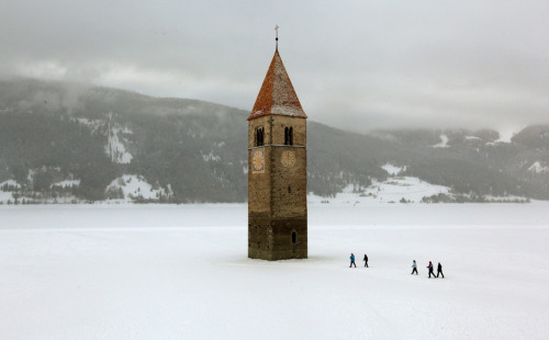[People walk on the frozen Lake Reschen reservoir beside the former church tower of the Village of Graun in South Tyrol in Northern Italy January 8, 2010.] Photo by Arnd Wiegmann *