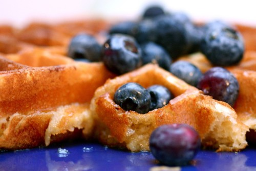 "Sunday morning waffles with lemon and blueberries 	It's been awhile since I posted a photo and recipe. Feels good to do it again.   	This is adapted from Mark Bittman's ""Everyday Buttermilk Waffles"" recipe found in the essential How to Cook Everything, mainly the addition of lemon and the use of greek yogurt instead of buttermilk.  	Ingredients:  	2 cups all-purpose flour 	1/2 teaspoon salt 	2 tablespoons sugar 	1 1/2 teaspoons baking soda 	1 1/2 cups 2% greek yogurt thinned with 1/2 cup skim milk 	2 eggs, separated 	4 tablespoons (1/2 stick) butter, melted and cooled 	1/2 teaspoon vanilla extract 	1/2 lemon 	Butter for greasing the waffle iron  	Preparation:  		Combine the dry ingredients in a large bowl. In another bowl, whisk together the yogurt, milk, and egg yolks. Stir in butter and vanilla. 	 		Grate lemon zest into the wet mixture, then squeeze lemon juice into bowl. 	 		Brush the waffle iron with butter and heat it. Stir the wet ingredients into the dry. Beat the egg whites with a whisk or electric mixer until they hold soft peaks. Fold them gently into the batter. If the mixture seems too thick, add more milk or a dash of a neutral oil like grapeseed oil. The mixture should be loose enough to pour but still thick. 	 		Spread enough batter onto the waffle iron to barely cover it; bake until the waffle is done, 3 to 5 minutes, depending on your iron (mine takes 2 minutes). Serve immediately."
