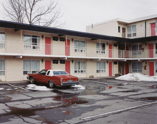 """Fairway Motor Inn"" from Alec Soth's book NIAGARA  Since I have it on loan, I'll be doing a short review soon of Alec Soth's photobook NIAGARA. I keep coming back to this particular photo from it but I can't imagine using it with a review of the book. Finding one photo to represent Soth's work in NIAGARA will be very difficult, but what I'm sure of is that this photo isn't it. Not that it's the odd photo out but others would probably be better. This photo, however, is perhaps my favourite of all the photos in NIAGARA. Somewhat odd since other photos in the book speak to me more but perhaps understandable because I wish I had whatever magic Soth put into this one.  Soth converts the mundane into the fascinating in it. There's an abundance of lines criss-crossing it, there's sparse colour except for the red doors which match perfectly with the red Cadillac. Delicious repetitions. The grey sky and light, the patchy wet asphalt, the barren tree; desolate. I'm not sure that the red doors and car manage to provide an uplifting counterpoint to the desolation rather than highlight it. Still, the melting snow is a sign of spring so maybe things aren't that bleak. ""Fairway Motor Inn"" still feels colder and more detached than much of the photos from NIAGARA.  But it makes me feel like I'm there. Perhaps in a movie, standing there in the parking lot  wondering what's behind those doors and what the plot is."