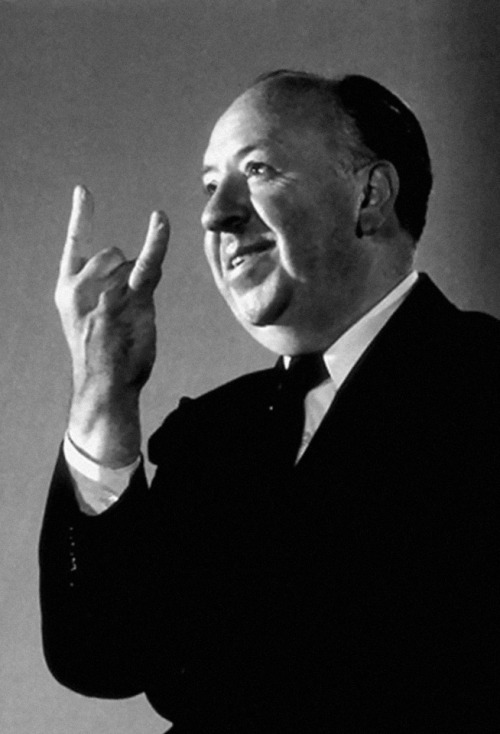 Alfred Hitchcock, throwing some horns  After reading Wikipedia's entry on the various cultural meanings of this gesture, we have concluded that he is either rocking out to some Black Sabbath, warding off an Italian giving him the Evil Eye, or telling a Cuban man that his wife is having sex with the neighbors.