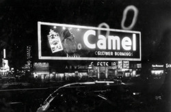 "timessquarestudio:  Camel Smoke Ring Billboard designed by Douglas Leigh, 1941 ""Times Square is the most familiar and most frequently reproduced fragment of urban real estate on the planet."" James Traub Since its beginning just over a hundred years ago, Times Square has been through many incarnations, each one a reflection of the social and economic condition of its time. The square, which is not technically a square, has gone from being the epitome of urbanity in the early decades of the 20th century to the urban collapse of the 60s and 70s. Its revival in the early 90s, which many New Yorkers decried as the Disney-fication of Times Square, has led to its present guise as a capital of popular culture, with the corporate headquarters for such giant media companies as Condé Nast, Viacom and Reuters competing for space with the world's busiest McDonald's outpost and the largest Toys 'R Us store. Yet what really attracts the thousands of tourists daily is its manifestation of global marketing, Times Square's famous ""Spectaculars,"" so-called since before World War I. The first billboard on Times Square went up on Broadway in 1904, and by 1907 electric billboards began to dazzle the crowd. The most eye-catching early billboards were designed by O.J. Gude, dubbed the Sign King of Times Square, who in 1917 installed a 200-foot long spectacular on the west side of Broadway between 43rd and 44th, complete with 12 gleaming moving spearmen. Gude also cunningly joined the Municipal Arts Society, a leading opponent of big signs at the time, and influenced the city to adopt zoning ordinances that eliminated big electric signs anywhere in midtown except Times Square.  The man who dominated the billboards from the mid-30s is the pioneering lighting designer Douglas Leigh. Some of his most memorable and spectacular signs for Times Square include A&P's sign for Eight O'Clock Coffee with clouds of steam emanating from a large cup of coffee and a Camel billboard that blew smoke rings from a steam generator. For Pepsi Cola, he designed a spectacular that featured a 120-foot waterfall pumping 50,000 gallons of water a day. Leigh's creations led to ever more innovative, colossal and dazzling displays on Times Square. Today the leading spectaculars are made up of millions of L.E.D.'s, capable of transmitting live footage and unimaginable pyrotechnics. As befitting the current environmental consciousness, 30 of the spectaculars in the area have switched to wind power via an electric supply agreement with ConEdison. The rent of these billboards, which run from $100,000 to $260,000 a month, has rendered the 1 Times Square building–the very one that lends its name to the square–empty of tenants except on the first 3 floors. The building is far more profitable to run as a billboard. With millions of people flocking to Times Square every year, and billions of people around the globe watching it daily on the news and on New Year's Eve, advertising here has become a premium. Tourists come to gawk at the signs, which feeds their attraction for advertisers, who dream up ever more spectacular creations. But in the end, what makes this carnival of lights in Times Square different from Las Vegas? What will be the future incarnation of Times Square if it is to avoid devolving into Las Vegas? As it has done over a century, Times Square will undoubtedly change as the city of New York moves forward in the 21st century. As James Traub wrote, ""The last word on Times Square will never be written."" - posted by Ngoc Minh Ngo"