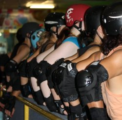 likeababeouttahell:  Derby girls in unison. Taken by the estimable Madam Kaos. (See that girl with the ridiculously pale arms in the red helmet with a skull on it? That's me, pre-haircut.)