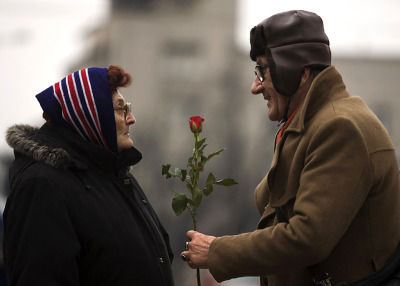 inothernews:  AS EQUALS A man offered a rose to a woman to mark International Women's Day in Belgrade, Serbia, Monday. (Photo: Marko Djurica / Reuters via the Wall St. Journal)