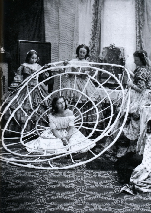 liquidnight:A woman needed several helpers when putting on a crinoline, circa 1850  From 1000 Dessous: A History of Lingerie by Gilles Néret [see also&also;]