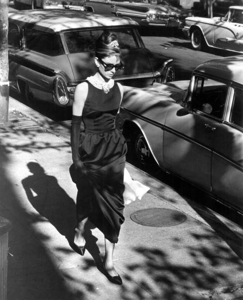 "Audrey Hepburn in Breakfast at Tiffany's (1961, dir. Blake Edwards) (via) ""The ragbag colors of her boy's hair, tawny streaks, strands of albino-blonde and yellow, caught the hall light. It was a warm evening, nearly summer, and she wore a slim cool black dress, black sandals, a pearl choker. For all her chic thinness, she had an almost breakfast-cereal air of health, a soap and lemon cleanliness, a rough pink darkening the cheeks. Her mouth was large, her nose upturned. A pair of dark glasses blotted out her eyes. It was a face beyond childhood, yet this side of belonging to a woman. I thought her anywhere between sixteen and thirty."" -Truman Capote, Breakfast at Tiffany's (1958)"