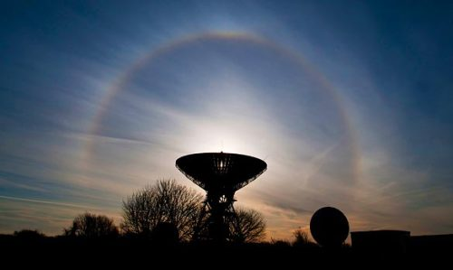 "An engineer from Herefordshire manages to catch a sun halo while carrying out maintenance work.  Sun halos occur when water droplets in high-altitude cirrus clouds  freeze and  form crystals.   Paul Simons, the Times weatherman, said: ""As the sunlight goes  through  the ice crystals it is as if it's going through a glass prism. The light  is  beamed out into an arc. The best Sun halos can be found in the Arctic  and  Antarctic — but in Britain at the moment we have the ideal conditions.""  Photo: Ian Collins via the Times website"