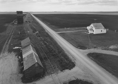 """From Country Elevator, Red River Valley, 1957"" by John Szarkowski, via Lens Culture  I must have read somewhere, at some point, that John Szarkowski was himself a photographer, but it doesn't seem to have registered with me at the time. So when Jeff Curto, in an episode of The History of Photography podcast, described Szarkowski as a ""photographer in his own right"", and then followed it up with his photos, I was surprised. And I might say surprisingly so since I should have known already or at least somewhat expected it.  The reason for this fact finally sticking in my head is probably that this time I was presented with his photos and not just his name in connection with the photographs of others. Szarkowski the curator's legacy – he was director of photography at The Museum of Modern Art in New York from 1962 to 1991 – hugely outweighs the legacy of Szarkowski the photographer, if that can be separated as easily as that. If it can't, I guess it only makes his photos more interesting. I'd like to say that given examples such as the photo above, that Szarkowski the photographer could stand on his own without help from Szarkowski the curator. But, given just how much Szarkowski the curator has influenced how we look at photographs, I could very well be mistaken.  As an aside, if you haven't heard of The History of Photography podcast, by Jeff Curto, before, I suggest you try watching an episode. As Curto describes the podcast himself, it ""is recorded during class lectures for History of Photography, Photo 1105 at College of DuPage. The podcasts are intended as review for students in the class, but thousands of people around the world have found them useful to their education as photographers."""