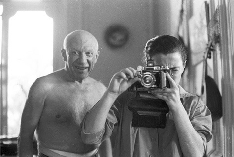 a smiling picasso looks over jacqueline's shoulder as she aims her camera at the photographer. villa la californie, 1957 by david douglas duncan