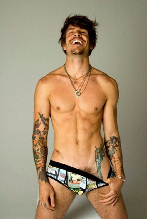 whytheyrehot:  Why He's Hot: This sexy bastard is Mateus Verdelho. Say that shit out loud: Mateus Verdelho. That's the kind of last name any girl would be proud to adopt, and could make any first name sound good. Bertha Verdelho. Gertrude Verdelho. See what I mean? It's Brazilian. He's Brazilian. And you thought they only produced really hot chicks! OMG his tattoos. He's covered in them, from head to foot. Actually, to toe. Just look at that strategically placed pistol. Have you ever seen anything sexier? Damn: I'd like to trace it with my tongue.  That smile is a fucking pussy magnet. Look at it. No, LOOK AT IT. Hey! Put your pants back on - it's not literally a pussy magnet! I don't think you have to wonder why it's been the background for WTH's contact form all this time. Oh, what's that you say? You want to see another photo of him in that bear hat? Alright, here you go.  He's a model, and he makes every thing look sexy. No seriously, have you ever seen someone sitting around eating Burger King look so good? I didn't think so. He has no problem being naked, either (which is a definite plus). His body is ridiculous. Actually, I think it may call for the use of the word ridonkculous. Did you see those obliques? What about these abs? And his perfect man nipples? Did he just make nipple piercings on a dude sexy?! YES HE DID. Also, please to enjoy Mateus in glasses.   W. T. F. So hot