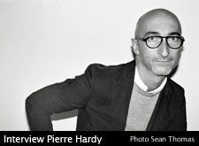 Interview with Pierre Hardy Archive February 2009  studiohomme: How do you dress these days? Pierre Hardy: As always: sweater, stripe, check or Oxford shirt, jeans, red socks. I wear the new Levis jeans with trouser pockets all the time. sh: Which are you favourite labels? PH: Balenciaga, Margiela, 45RPM, Thom Brown, Band of Outsiders, Patagonia, Comme des Garçons, Jil Sander, Hermès and Ralph Lauren. sh: Which shoes are you wearing? PH: Short boots, loafers, black Oxford shoes, white sneakers and sandals for summer. sh: Do you have fetish accessories? PH: Yes, my Rolex watch and the Hermès Etrivière belts in any width. sh: What are you going to buy with studiohomme.com? PH: Shirts from Comme des Garçons and some pieces from Kitsuné. sh: What is the brand and model of your sport bag? PH: Pierre Hardy! The bag A in black leather…