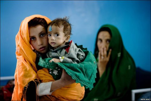 newfilosofee:  A young girl holds her nephew who is suffering from malnutrition at a therapeutic feeding centre. One in five children dies before their fifth birthday. -Afghanistan, BBC News