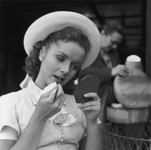 Debbie Reynolds, wearing a straw hat and applying lipstick behind the scenes of I Love Melvin - May 26, 1952.