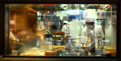 Japanese restaurant kitchen. It is kinda cool that you very often can see your food being made in front of you in Japan. I enjoy watching a good chef work, but it is also shows transparency. It is not like they into some hidden kitchen and put something in the microwave for you. Outside this particular restaurant they also had a little speaker where you could hear the sounds from the kitchen. They got nothing to hide here apparently. Photo is taken from from the outside in Shinjuku, Tokyo.
