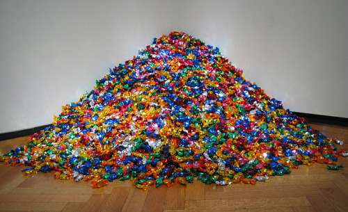 "nowmybutthurts:   portrait of ross by felix gonzalez-torres As I've gone on and on about this guy today, it's easy to see why he's one of my favorite conceptual artists. At first glance it would appear to be the perfect parody of contemporary art. ""Why, it's only a pile of candy!"" Those more inclined to actually interrogate it as a work of art might be more charitable. They might interpret the color, the texture. They might realize how the haphazard nature of the candy's piling makes it's final form mutable. And if they were bold enough, they might take a piece of the candy and eat it and enjoy it, and realize that this work of art gave the viewer some sort of tactile reaction and sense manipulation that a Monet or Martini or Mondrian couldn't. Ross was Gonzalez-Torres's lover, who died of AIDS. When Ross was first diagnosed, his doctor told him his ideal weight was 155 pounds. Every day, the candy is weighed and 155 pounds is placed out. Here the candy IS love/happiness/sweetness/togetherness. Visitors to the museum are encouraged to enjoy a piece. It's a giving, generous work of art; but with a dark edge; for as the candy gradually diminishes it symbolizes Ross's weight loss due to AIDS. However,  each morning the candy is weighed out and replenished,so that in this artwork (unlike life) Ross may live on forever.   via keeptheballrolling, absurdlakefront, shapeandcolour:  Two years ago, I went as this piece for Halloween. I wore all white and tied a piece of Gatorboard to my stomach, on which I piled candy and rubber cement. Needless to say, I left a trail of crushed candy and pretension across at least two boroughs."