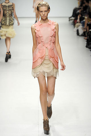 "I had actually blogged about a piece from the Christopher Kane 2009 RTW collection before (Frieda Pinto's absolutely gorgeous black number) but I never expected something so Chloe-like to also emerge. This lovely pastel number (generically named ""Scalloped Silk Dress"") has me gushing, seriously. You have the avant-garde that is Kane's modus operandi, and yet an unexpected softness. The layered/different-sized scallops are just parfait, and the color is just the right amount of saturated to last you through any spring season. Unfortunately, with knowledge comes disappointment. Of course, it's sold out. What once was discounted 80% (AHH! £3,227.77 to £645.55 [sorry, not avail on the US site]) is now out of my reach forever. Still, il y aura un jour …"