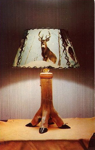 "WORLD'S TACKIEST LAMPS—PART 1 DEER HOOF LAMP No description on this card. Question is, are they real deer hooves? I say yes. On the internet I found:— Instructions on how to make a deer hoof gun rack— You can purchase a deer hoof coat rack (the lower portion of the deer's leg, bent at the joint, and attached to a log)— A seller on eBay currently has a ""VINTAGE VICTORIAN DEER HOOF PIN CUSHION, NICE"" with a Buy-It-Now of $69.99— A deer hoof bottle opener from a German souvenir website Reuse. Recycle. NEXT:  Is this man possessed???"