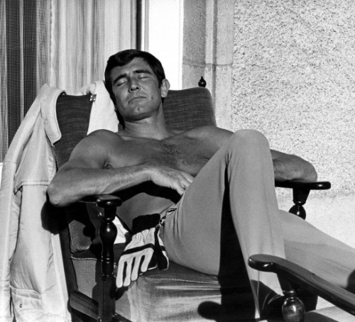 "Entirely gratuitous photo of George Lazenby sunning himself on the set of On Her Majesty's Secret Service (1969, dir. Peter Hunt) Q: ""Why did you give up the role of James Bond?   I've heard three stories.  I've heard that your relationship to Peter  Hunt lead to you being let go from the franchise, that Sean Connery  regretted not doing Majesty's Secret Service after  seeing it and wanted the part back, and that you took poor advice from  your agent.  What is the most accurate reason?"" Lazenby: ""The third is correct. I wanted to do the next one because  they offered me a million dollars under the table which is probably ten  million today. So I looked at my manager and said ""What's wrong with  that deal?"" and he said ""No. You'll die doing Bond because it's over. It's finished.""  It's hard for people to understand that, because we are  back in a Bond-type culture. At that time we were into hippie  culture. You'd have to put yourself into long hair and bell bottoms and  peace and love-consciousness to be able to understand what rung through  to me. Otherwise, right now, it looks foolish. Back then it looked  foolish, but money was not the ""in"" thing at that time. Love and peace  was in. Guys running around with suits and guns couldn't get laid. Honest to God. They thought you were a waiter or a cop or something. Nobody was wearing a suit. Not even Wall Street. They even took their  ties off. Unless you can put yourself in that time zone you'll  understand that it wasn't because I was that stupid, it was that I was  walking in Sean Connery's shoes and wanted to walk in my own."" (via)"