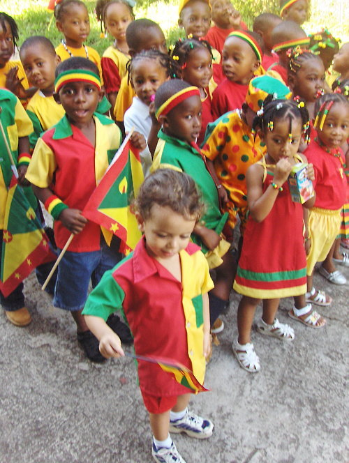 "Bean started going to school in Grenada when he was about two and a half. He was the youngest kid in the classroom, which worried me a little at first, but it worked out well in the end, because the older boys made him their mascot.  He loved school. He had a uniform, a yellow and white checked shirt and khaki shorts. His hair had never yet been cut, so every morning his father slicked it back into a neat (and manly!) ponytail. Then I we walked together the three blocks to a church with no roof. The roof had been blown off during Hurricane Ivan, and was being repaired the entire time Bean attended, and so the place was kind of like a construction site, which of course the child loved, because he gets almost as much glee from cement trucks as he does from chocolate.  I say the roof was missing, and it was, but Bean and his classmates were well-covered, because the church was two stories, the school was on the first and the floor of the second story was intact.  On Grenadian Independence Day, there was a class trip to Grand Etang, which is a beautiful natural lake in the rainforest that sits right in the center of the island. I tagged along, and it was a wonderful day.  I took this photo in front of the school, in the morning while we were gathered waiting for our bus to arrive. The kids are all dressed in their ""national colours"". Independence Day commemorates the end of Grenada's time as a colony of the British Empire. It should not be confused with Thanksgiving, which celebrates the anniversary of that time some United States Marines landed on the island, sent there by Reagan in response to the (socialist) Grenadian Revolution.  (A photo very similar to this one ended up in the inside cover of the Grenada Yellow Pages. Click here and here.)"