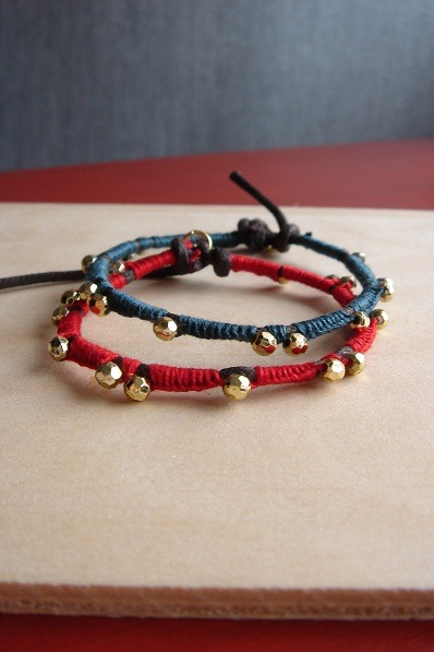 a leathery thread with golden cast bead / handwoven cotton and thin rope bracelet in dark teal in red