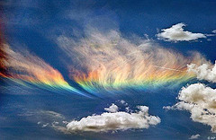 A 'circumhorizon arc,' sometimes inaccurately called a 'fire rainbow.'  When the sun shines through cirrus clouds at the right angle, the ice crystals in the clouds cause the light to refract (split) into its component colors. ~World Picture Network, 2006:   Real