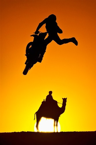 Australian freestyle motocross rider Robbie Maddison jumps during an trainingsession in the Sahara desert near the Giza pyramids as the sun sets in Cairo.