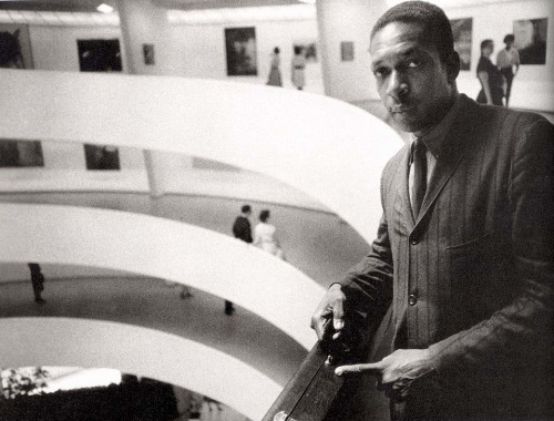 "William Claxton, John Coltrane at the Guggenheim Museum, New York, 1960 Claxton's photo teases us a bit, with Coltrane pointing at the case. It does give the feeling of walking up the ramp and bumping into John Coltrane. Unlike his great photograph of Donald Byrd, we miss the horn in the public space. Maybe there are other frames on the contact sheet with Coltrane playing in the rotunda? Maybe they were burned at the lab, like Capa's D-Day images. Maybe it never happened - but we can still imagine the sound of Coltrane playing ""Giant Steps,"" filling up the Guggenheim."