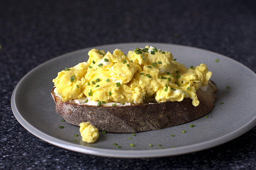 scrambled egg toast Simple and delicious. I would make almost exactly this, except make my eggs the slow-scrambled way. I don't know if you can tell from the picture, but there is a layer of goat cheese AND chives between the egg and bread. Need I say more?