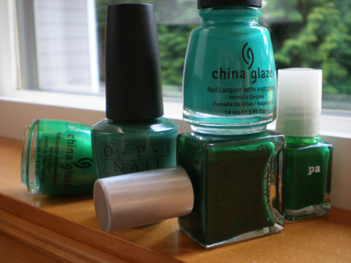 "A few of my greens, in anticipation of the new Essie green (which I really need to buy).  L-R: China Glaze ""Paper Chasing"" , OPI ""Jade is the New Black"" , China Glaze ""Four Leaf Clover"", Rescue Beauty Lounge ""Recycle"" , Pa ""A96"" (named after a daughter I think)."