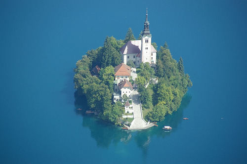 The island of Lake Bled in Slovenia.  It is about 100 km north of Trieste, Italy. It has a church, the  Pilgrimage Church of the Assumption of Mary, with 99 steps and a  52-metre tower.  It took the place of an ancient temple to the goddess Sieba. On the north shore  of the lake is Bled Castle. See it on Google Maps at 46.3623,14.089794 bowfolk:  ladollhouse:  jesuisperdu:  via fuckyeahglobetrotters:  Island of Bled, Slovenia