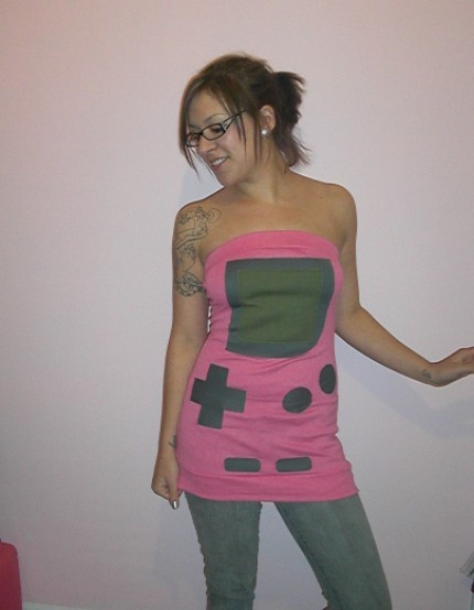 "Pink Game Boy Color tube top by SewOeno. The designer used her Game Boy tube dress as the basis for this top, remaking it in pink fabric with grey buttons to mimic the look of the pink Game Boy Color. It's a more summery wearable game console! I wonder if she plans to make the full range of Game Boy Color… colors? Not Atomic Purple, of course — being transparent, it's not exactly well-suited to clothing. See also: LowRez ""GB"" shirts and more"