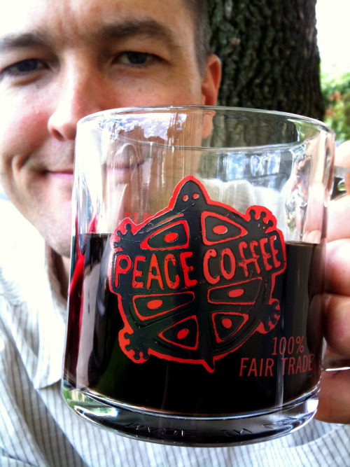 "Mugshot Monday - ""Peace Coffee 100% Fair Trade"" glass mug w/Twin Cities Blend by  Peace   Coffee. I forgot my milk today. I do like milk in my coffee — I use Silk Unsweetend Soy Milk to be specific. And I drink soy milk because I have high-ish cholesterol. Anyway, as it turned out, today was an okay day to forget the milk because I liked how awesome the Peace Coffee logo on the glass mug looks against black coffee. We'll just chalk it up as destiny, I guess. Sidenote: Check out the photo I accidently snapped whilst catching my iPhone from the same photoshoot as the above photo. Is it art?"