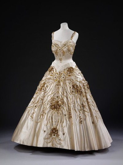 Evening dress worn by Queen Elizabeth II on a state visit to Paris in  1957 with gold and white beadwork. The dazzling, jewel-like details of the embroidered design include miniature bees, grasses, wheat and wild flowers. The design of this single-occasion gown diplomatically refers to French motifs, including the flowers of France and large gold bees, the emblem of Napoleon. It was intended to both compliment the French nation and draw attention to the Queen. (The Met Museum)