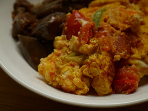 The first dish. eggs scrambled with tomatoes.Eggs scrambled with tomatoes is a classic Taiwanese home-cooked dish. I don't actually remember what the first dish I ever made was - steamed rice? Brownies from a mix? - but surely this is one of the first things I learned to cook on the stove. Sometimes I burned the scallions, undercooked the tomatoes so the whole dish was too watery, stirred the scrambling eggs so enthusiastically that everything broke apart into clumps, added too much salt or too little, both cardinal sins. Sometimes the scallions were too raw or the tomatoes too mushy. We would sit down to dinner, me folding my legs under me in the window seat, and my parents would (kindly, gently) point out what I had done wrong, and how I could do it better. Sometimes, though, they would be just right.A while back, some coworkers and I had an intense, trilingual debate over the proper way to cook scrambled eggs and tomatoes. There is no single, canonical recipe. Some people scramble the eggs first, remove them onto a plate, then cook the tomatoes and scallions separately. I don't understand this, because then the tomatoes and eggs don't stick together at all. Other people add ketchup, or wait until the end to add the scallions (sliced into two-inch logs) so they remain crisp and fresh. I also don't understand this, because I don't like raw scallions unless they are very thinly sliced. My own method has evolved over some twenty years, and now I can do it without thinking.I use Roma tomatoes, and slice them into chunks about 3/4 inch square, two tomatoes for three eggs. I slice a couple of scallions thinly on the bias, beat the eggs with a fork (if I were being properly Chinese, I'd use chopsticks for this), and heat a little oil in a frying pan. In go the scallions, and when they start sizzling, I add the tomatoes. I let the tomatoes cook until they soften, release their juices, then cook them a little longer until the juices are almost gone. Season with salt and pepper, pour in the beaten eggs. Fold the eggs over on themselves as they set, turn golden around the edges. Once in a while, I manage to get everything to hold together into a soft frittata; usually it falls apart in irregular wedges. It doesn't matter. It's always delicious.