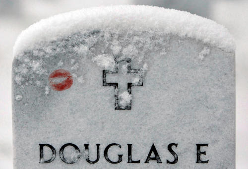 A red lipstick mark is covered with snow on the tombstone