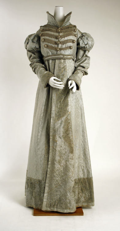 A circa 1820 pelisse of American origin. The pelisse originated as a short, fur-lined military coat that was worn hanging from the shoulders. The purpose of this coat was supposedly to protect from sword cuts, but it soon became a fashion staple for officers. During the Napoleonic Wars women's fashion began to incorporate many military inspired designs, and the long woman's pelisse became a staple of Regency fashion.