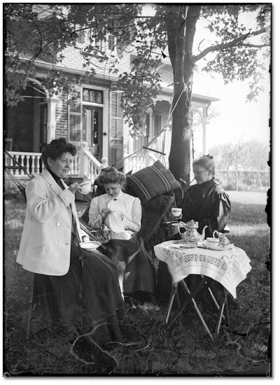 Three ladies taking tea outside, [between 1898 and 1920]
